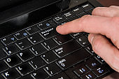 finger presses the backspace key, laptop and hand