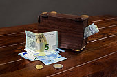 Euro money and wooden piggy bank on the table