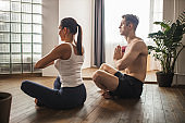 married couple meditating, do yoga exercises at home