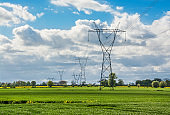 Electrical towers and a green meadow. Beautiful landscape in Poland