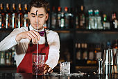 Barman holding a long spoon and glass filled with ice cubes on the bar counter