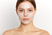Portrait of relaxing shirtless beautiful woman with cream lotion on face