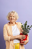 Active senior woman smiling at camera keeping potted plant in hands.
