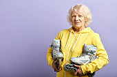 Active senior woman in yellow sports hoodie holding roller-skates posing indoors