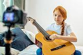 little caucasian girl play guitar at camera