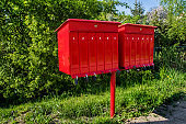 Red mailboxes with numbers by the road. Post office in Poland