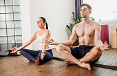 married beautiful couple meditating, do yoga exercises at home