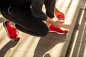 Runner getting ready jogging tying running shoes laces while sitting on track