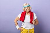 Elderly sportswoman with headband and red towel on neck, looking at camera