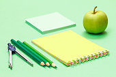 Compass, color pencils, notebook, note paper and apple on the green background.