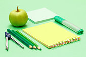 Compass, color pencils, notebook, apple and note paper on the green background.