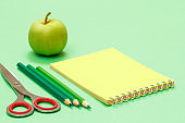 Scissors, color pencils, notebook and apple on the green background.