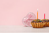 Birthday muffins with burning festive candle and gift box on the pink background.