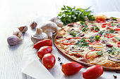 Fresh homemade pizza with tomatoes, salami, cheese and mushrooms