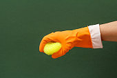 Woman's hand in protective glove with sponge on the green background.