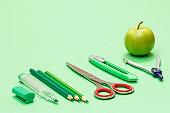 School supplies. Felt pen, color pencils, scissors, paper knife, compass and green apple.