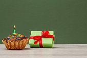 Birthday cupcake with burning festive candle and gift box on green background.
