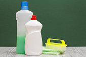 Bottles of dishwashing liquid and brush on the green background.