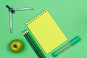 Compass, apple, color pencils, notebook and felt pen on green ba