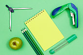 Apple, compass, color pencils, notebook, felt-tip pen and stapler