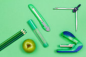 Color pencils, apple, felt-tip pen, paper knife, compass and stapler on green