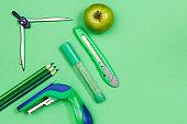 Pencils, compass, felt-tip pen, paper knife, stapler and apple on green table