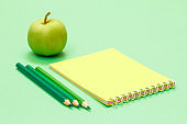Color pencils, notebook and apple on the green background.