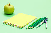Compass, color pencils, notebook and apple on the green background.