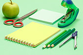 Compass, color pencils, notebook, note paper, stapler, apple and scissors on green background.