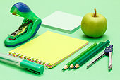 Compass, color pencils, notebook, apple, note paper and stapler