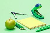 School supplies. Compass, color pencils, notebook, apple and stapler.