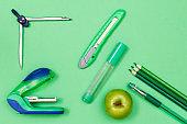 Color pencils, pen, apple, felt-tip pen, paper knife, compass and stapler on green background.