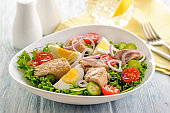Fresh vegetable salad with boiled chicken egg and fish.
