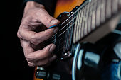 Guitarist hands and guitar strings close up.