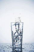 Clear mineral water splashes in a glass with ice. Fluid in motion.
