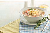 Vegetable soup with cheese and fresh herbs. A large portion is served in a deep white plate.