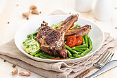 Grilled lamb chops with a garnish of green beans and fragrant butter.