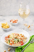 Shrimp salad with fresh vegetables, cheese and croutons. A large portion is served in a deep white plate.