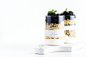 Milk yogurt with blackberries and homemade granola and Breakfast cereal in a glass on white background
