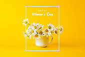 "Daisy in white iron circle and the text ""Happy Womans Day"" on yellow background"