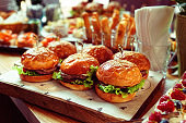 Burgers and another food on restaurant table, toned