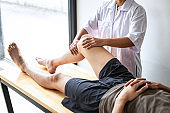 Female Physiotherapist working examining treating injured leg of male patient, Doing exercises the Rehabilitation therapy pain his in clinic