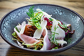 Smoked ham salad with fresh leaves, green peas