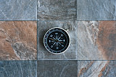 Old compass on stone floor background, copy space