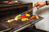 Chef is cooking vegetables in charcoal grill, toned