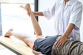Doctor or Physiotherapist working examining treating injured leg of athlete male patient, Doing the Rehabilitation therapy pain in clinic