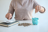 Young woman putting coins into piggy bank planning growing saving to strategy with money box for future plan fund of travel, education, home and retirement