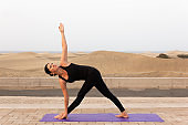 Slim woman in black sportswear practicing parivrtta trikonasana by Maspalomas sand dunes
