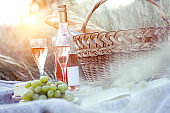 "Summer - Provencal picnic in the meadow.  baguette, wine, glasses, grapes, Cheese brie, baguette in a basket ""n"