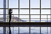 Lonely passenger standing with cellphone and drinking coffee cup by airport terminal glass window